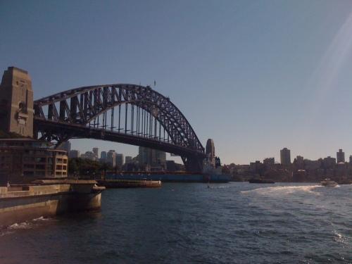 Picture of a boat passing under Sydney Harbour Bridge